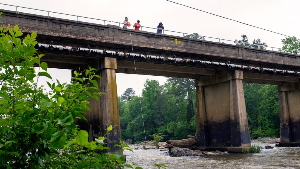 The Knappe group take water samples from a bridge over the Haw River.
