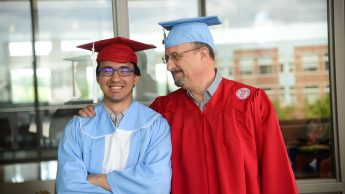 Timothy and David Calhoun smile in cap and gown