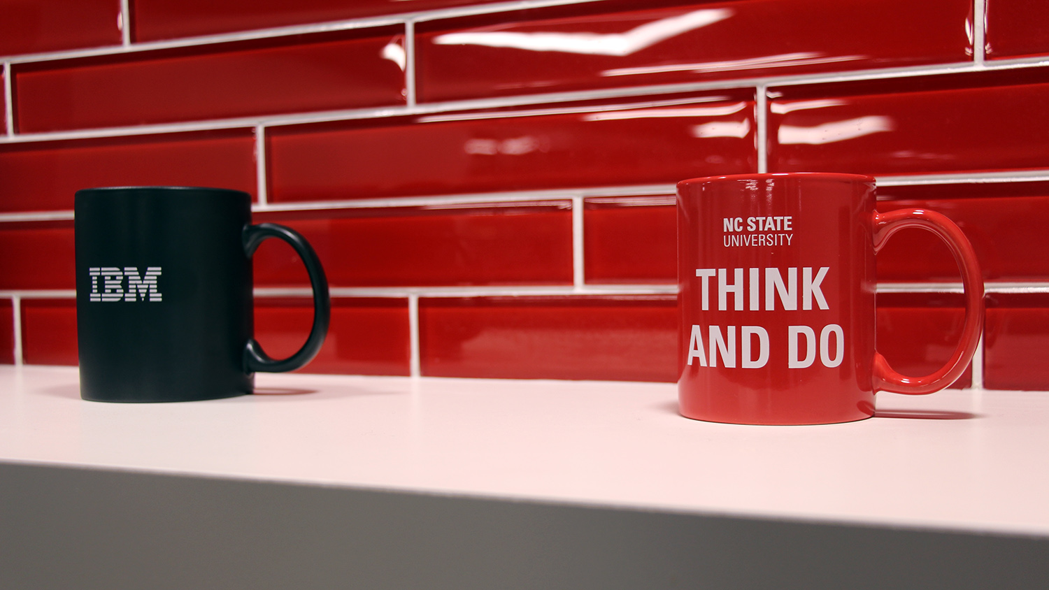 An NC State coffee mug and an IBM coffee mug on a shelf.