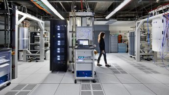 A woman walks across the floor inside IBM's quantum computer.