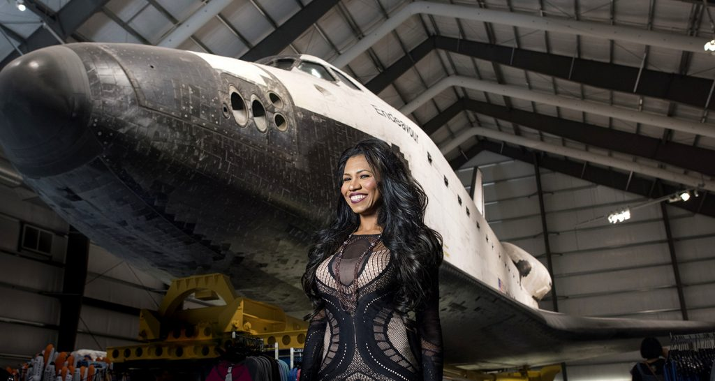 Rocket scientist Olympia LePoint stands in front of a space shuttle in a NASA hangar.