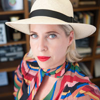 Close up shot of Tiffany Shlain wearing a white bowler hat and bright red lipstick.