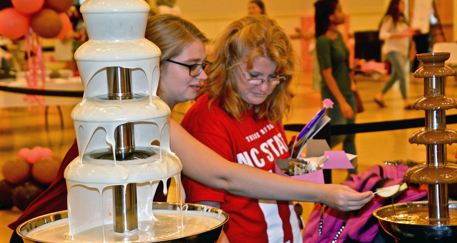 Two young women sample a treat at the NC State chocolate festival.