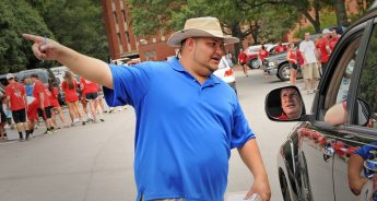Transportation employee directs a dad on where to park after unloading during move-in.