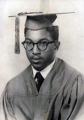 Graduation photo of Holmes in cap and gown.