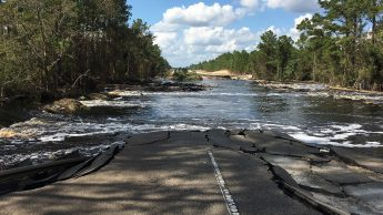A cracked highway disappears into flood waters.