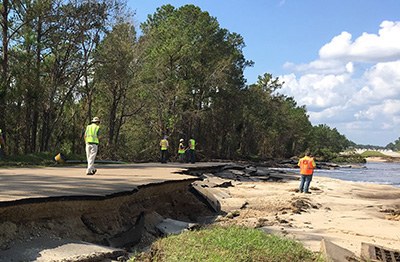 People stand on a washed-out road.