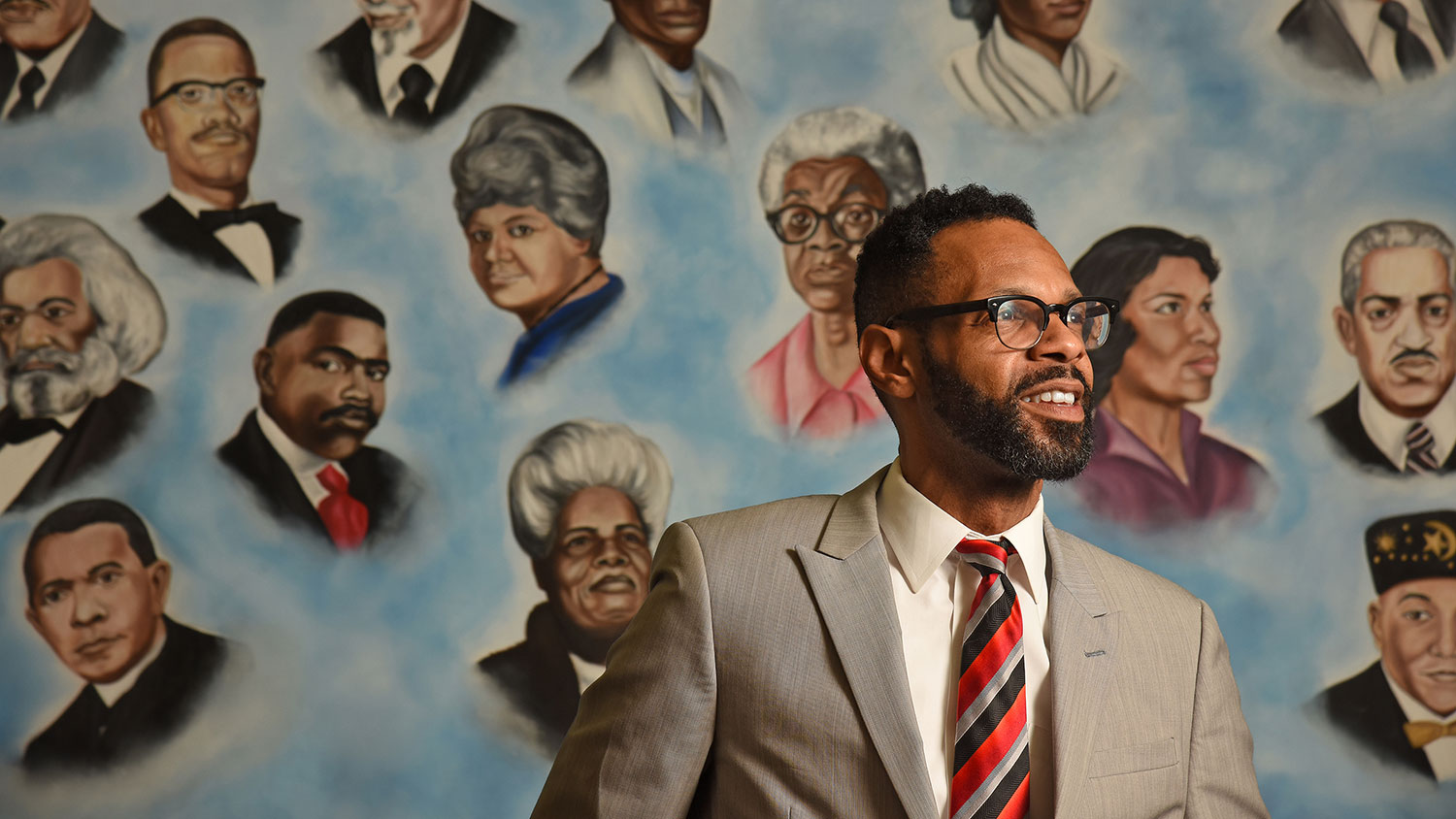 Moses T. Alexander Greene standing against a mural with pictures of black historical figures.