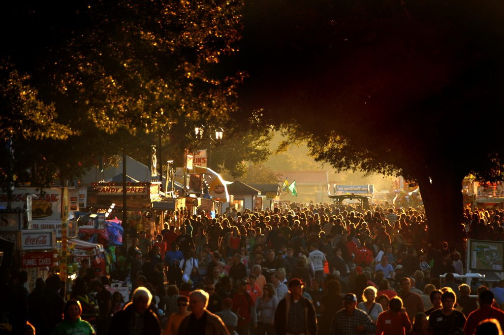 A huge crowd of fairgoers on the midway is illuminated by a warm autumn light.