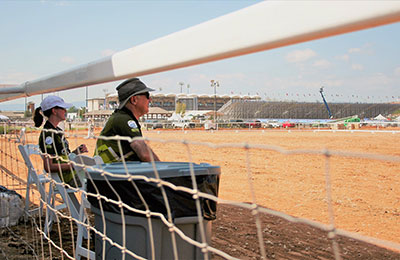 A man and a woman sitting on chairs just inside a horse track