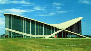 The curving, modern Dorton Arena is seen on a green expanse of lawn in a postcard image from the 1950s.
