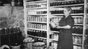 A woman looks carefully at a jar of preserves in this black-and-white image. Behind her are two shelves full of neatly-arranged jars.