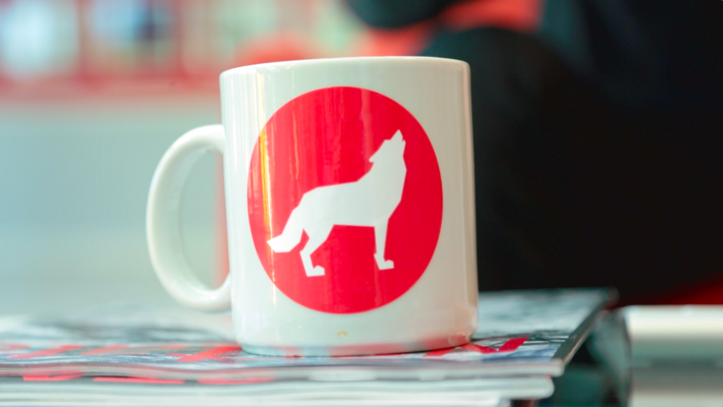 NC State coffee mug sits on top of a stack of NC State Alumni Association magazines.