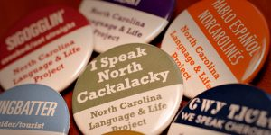 "Colorful buttons sport phrases such as ""I speak North Cackalacky"" and ""dingbatter"" -- slang phrases from traditional state dialects."