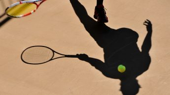 Photo of a tennis ball being struck by a tennis racket.