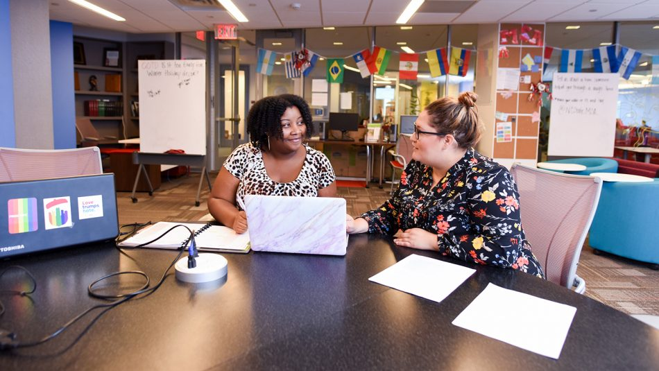 Staff members Leah Young and April Hammonds work together in the lobby of Multicultural Student Affairs.