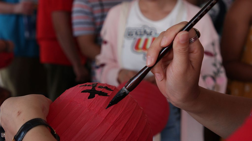 A person painting calligraphy on a Chinese lantern
