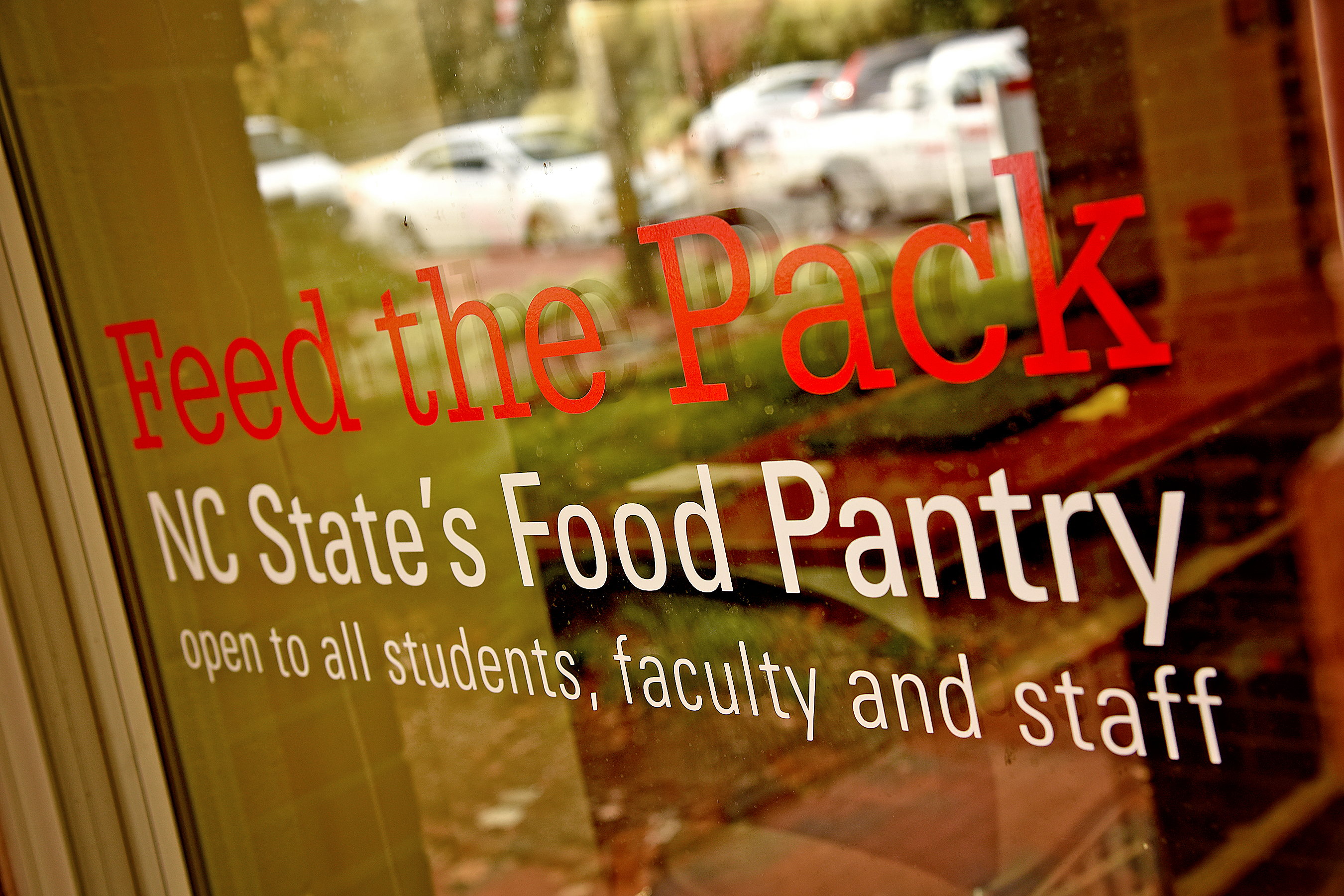 "Sign on glass door reading ""Feed the Pack, NC State's Food Pantry, open to all students, faculty and staff"""