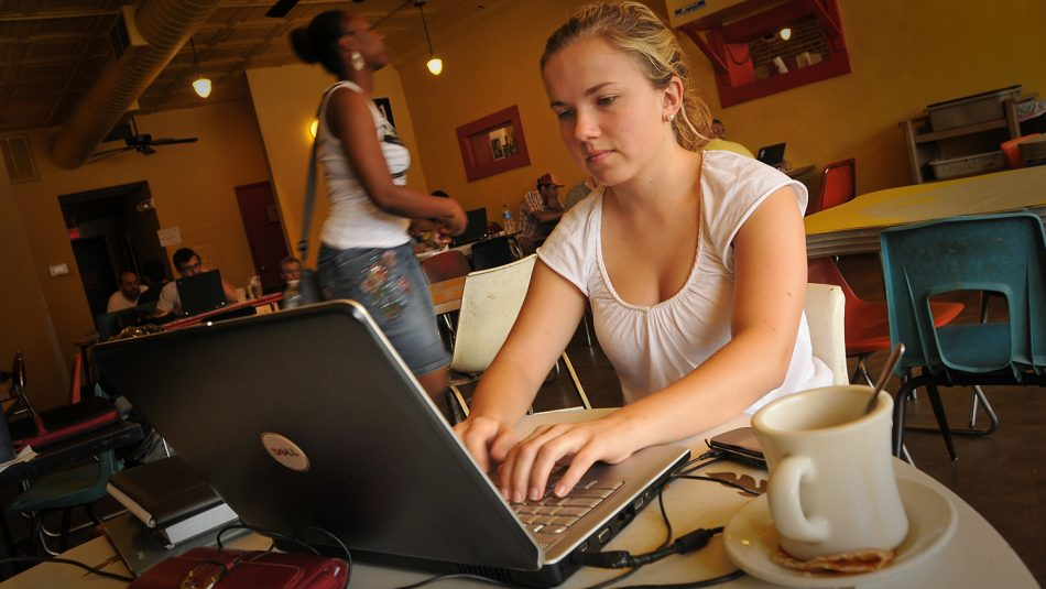 A young woman works on her laptop at a local coffee shop.