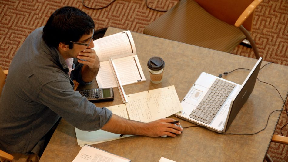A student studies in the library with his laptop and books open, a cup of coffee at his side.