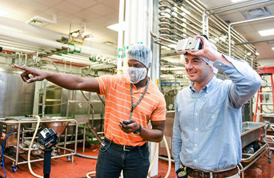 Two men in a dairy processing facility using a VR headset