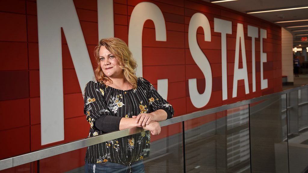 """Student Alison Plumley stands in front of the words """"NC State"""" at Talley Student Union."""