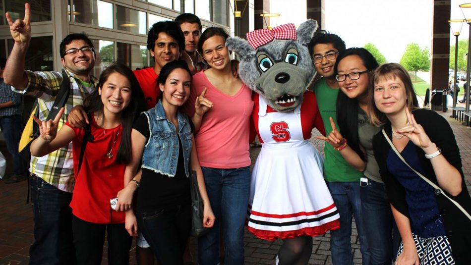 International students pose for a group shot with the mascot Mrs. Wuf