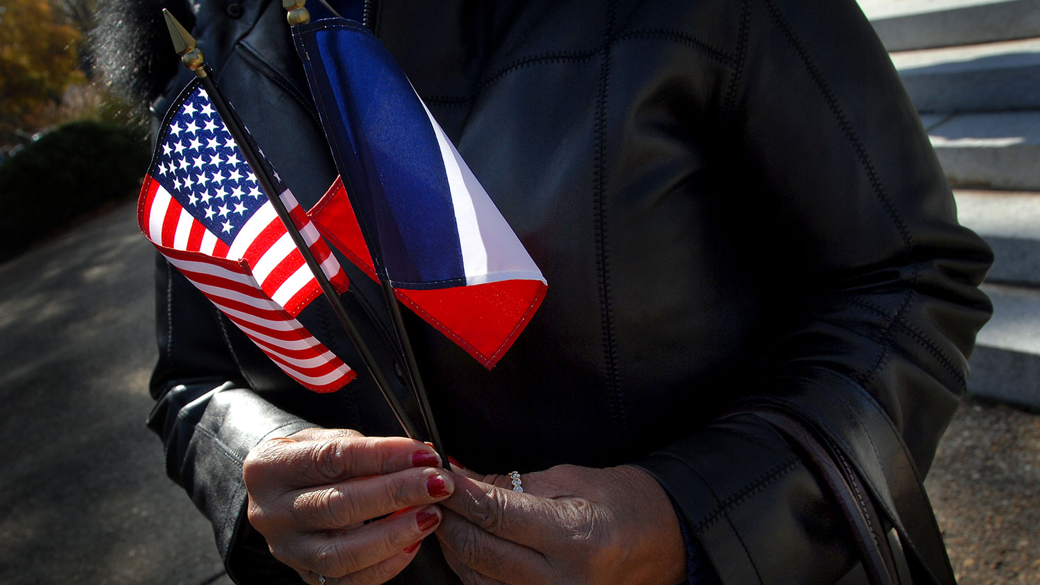 Hands holding American and French flags on Veterans Day