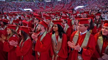 Graduates applaud their official conferment of their degrees.