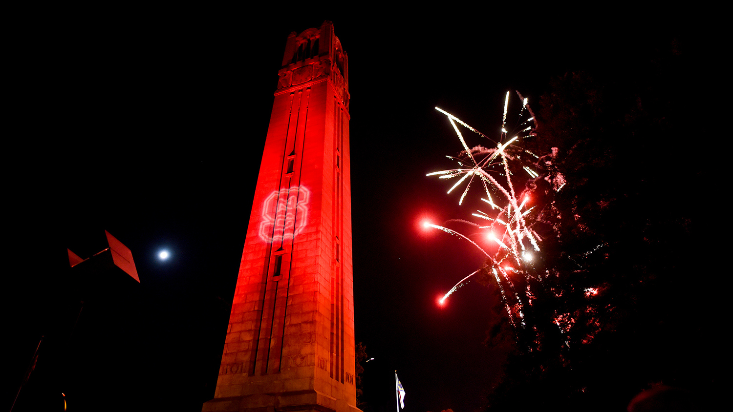 Photo of Belltower lit red with fireworks.
