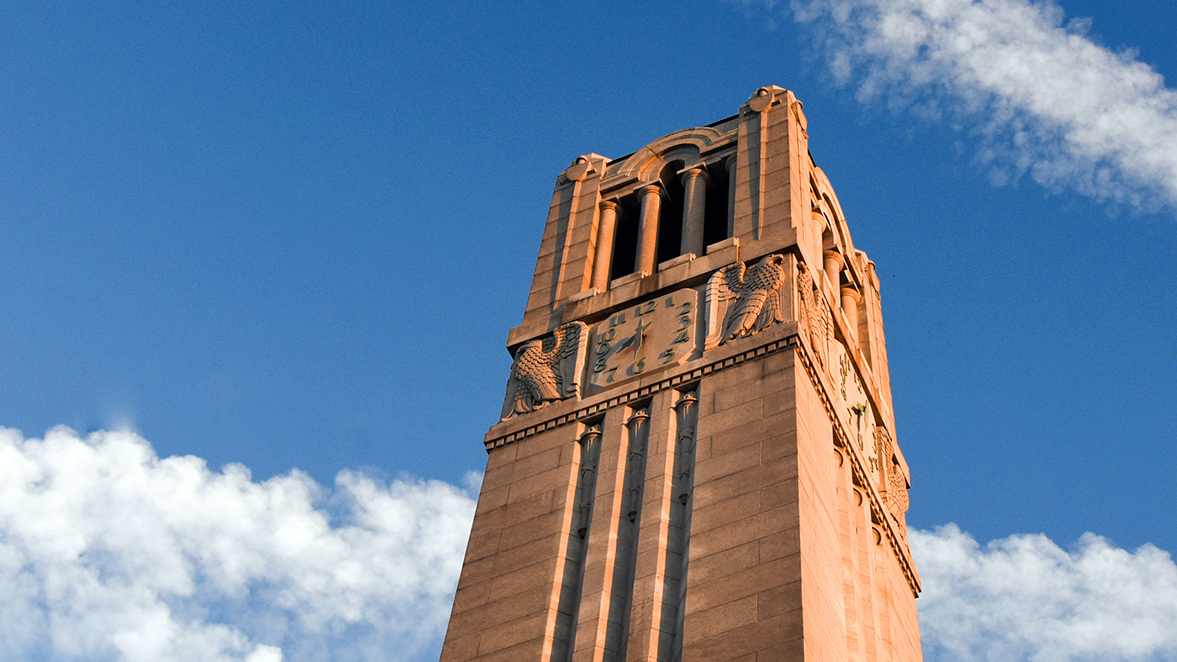 The NC State Belltower against a blue sky.