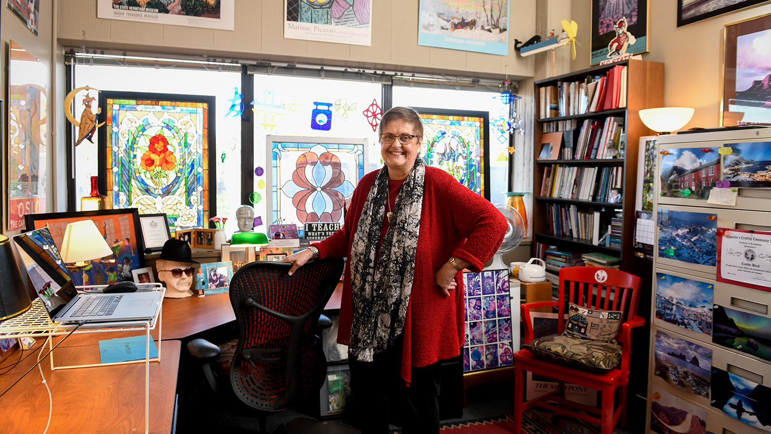 Candy Beal stands in her office before a large stained glass panel and many eclectic decorations.