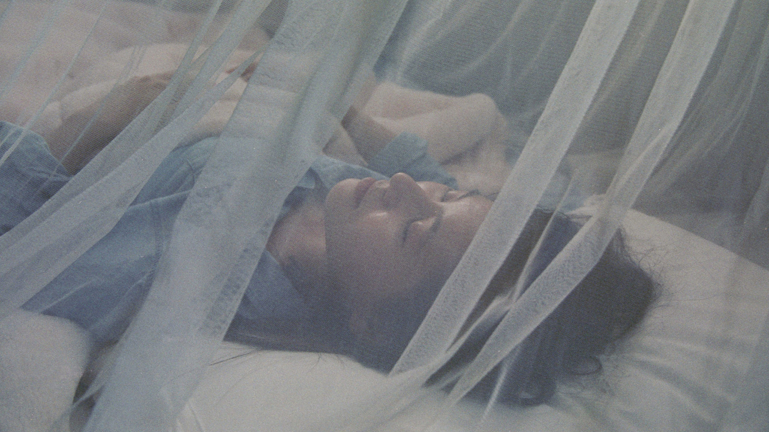 Woman sleeping under mosquito net.