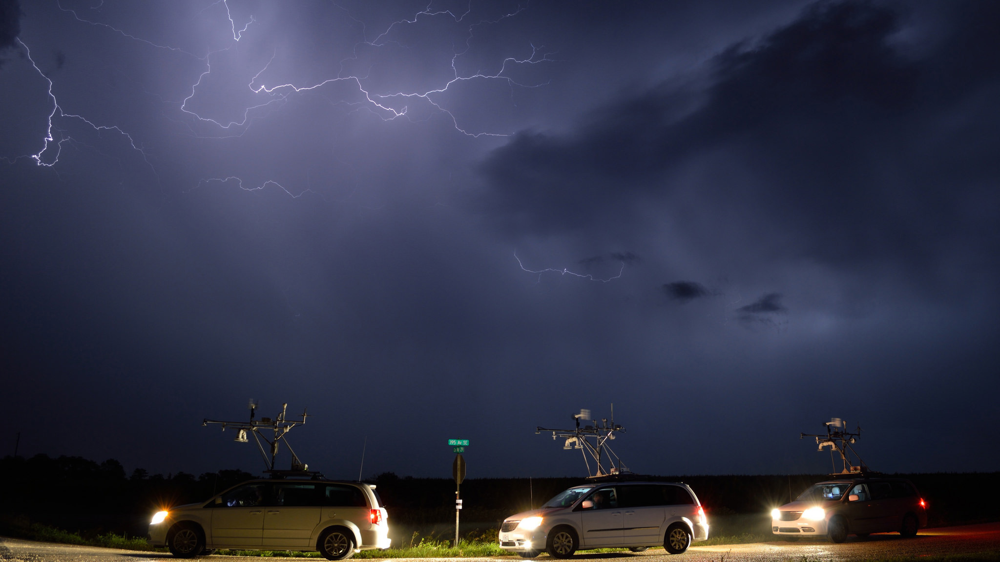 Research vans are silhouetted against a night sky streaked with lightning