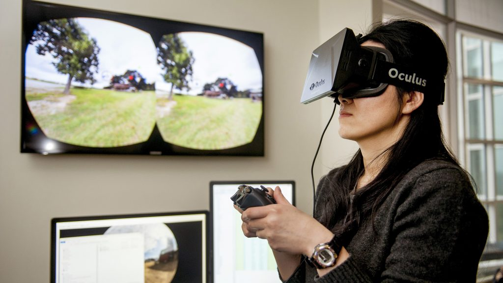 A student looks through virtual reality goggles and uses a controller