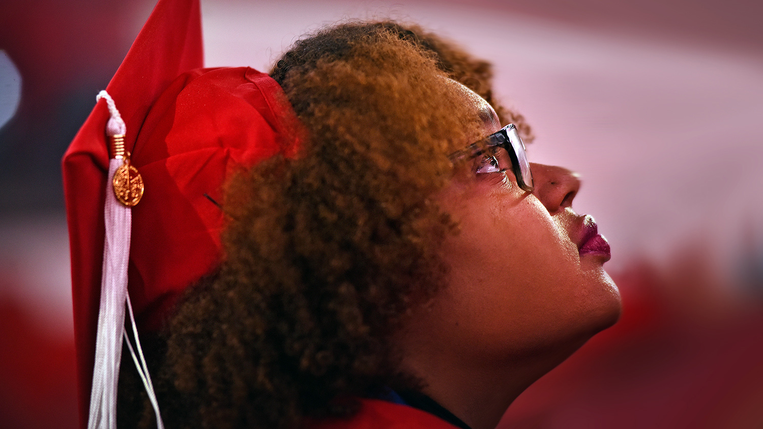 An NC State student stares upward during graduation.