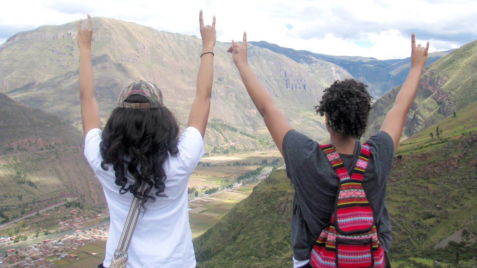 Two NC Stat students throw up the wolf hands while on study abroad.