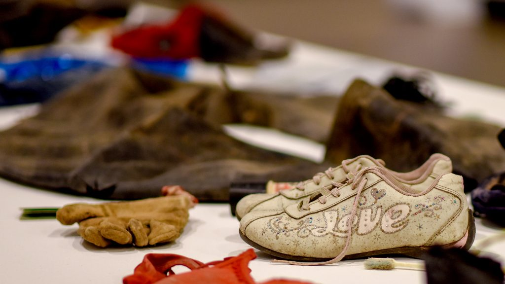 Sneakers, a glove and a deflated inner tube on display in the Gregg Museum.