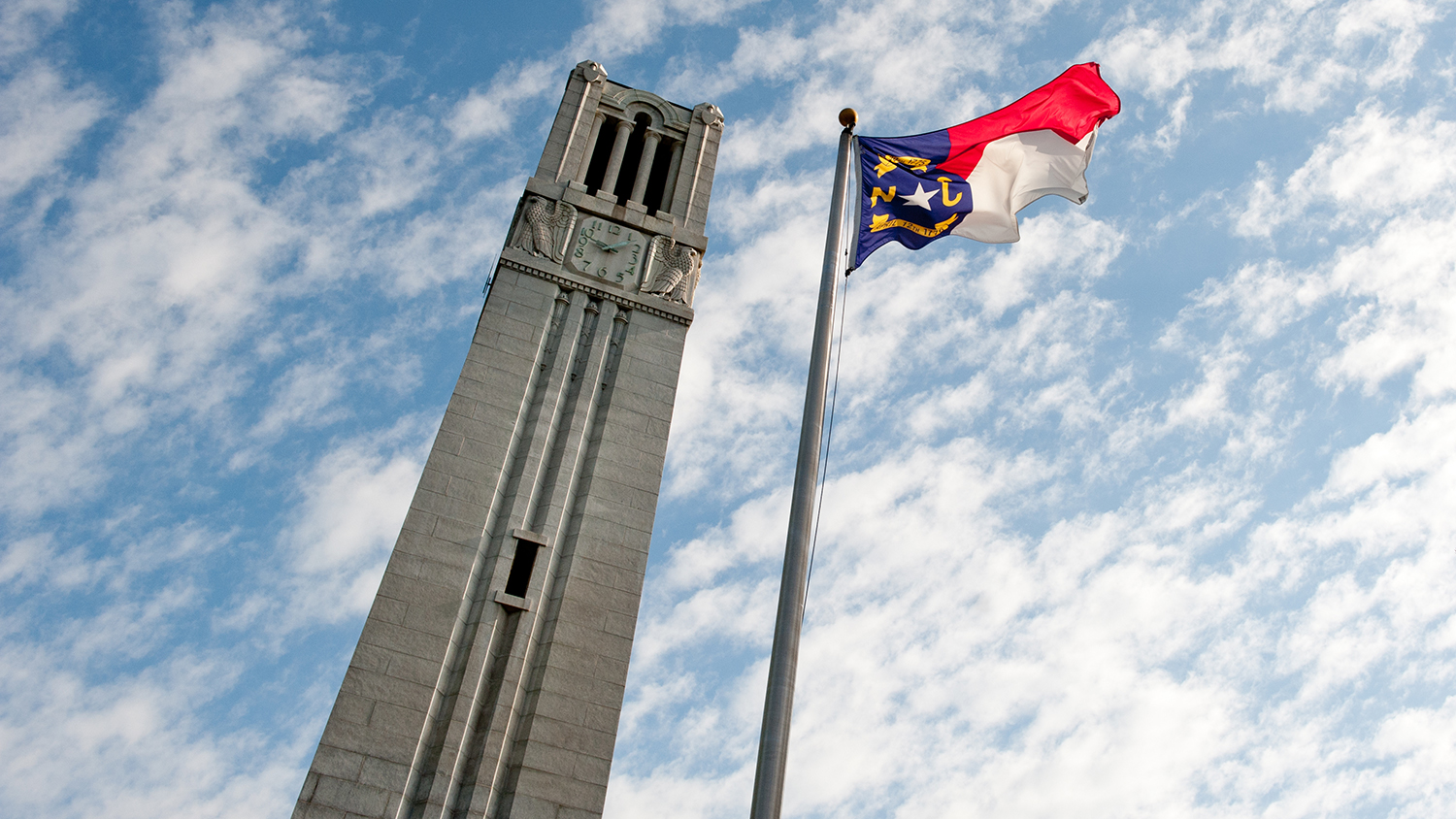 NC State's Memorial Belltower and North Carolina state flag