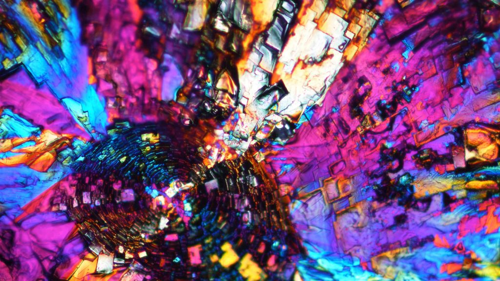 An unedited polarized light microscope image shows the crystal formation of a special type polyhedral oligomeric silsesquioxane (POSS) solvent-casted with chloroform.