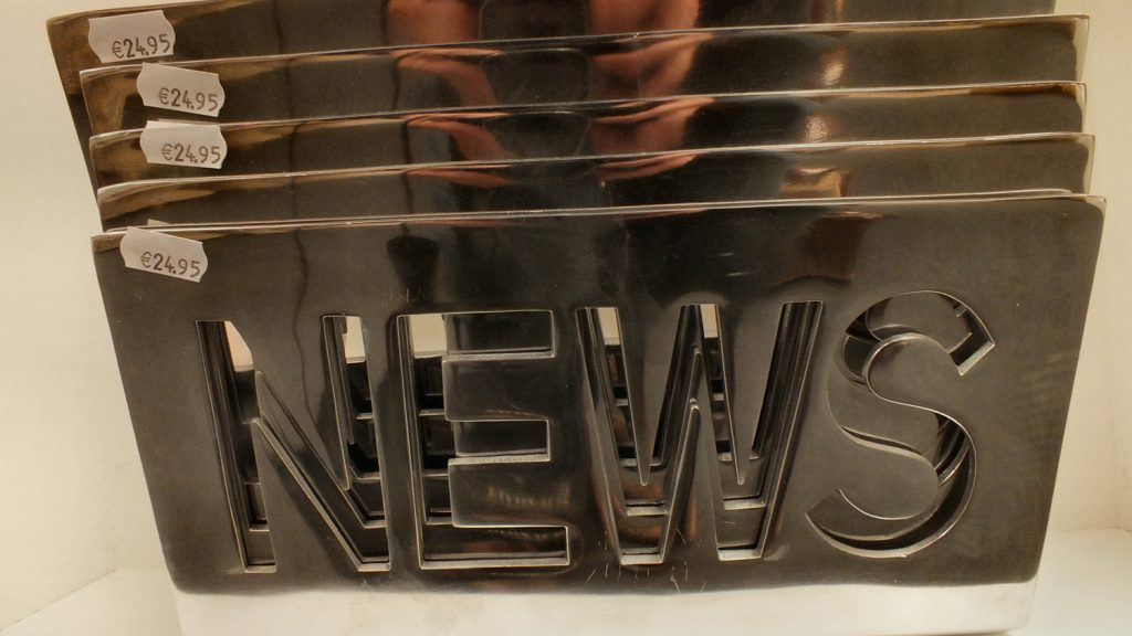 "metal sign that says ""news"""