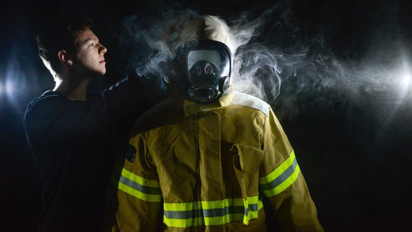 A researcher tests a fire hood atop a turnout suit as smoke swirls around it.