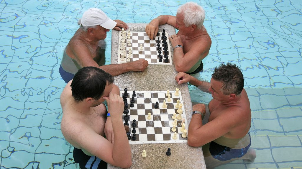 old men playing chess in a swimming pool