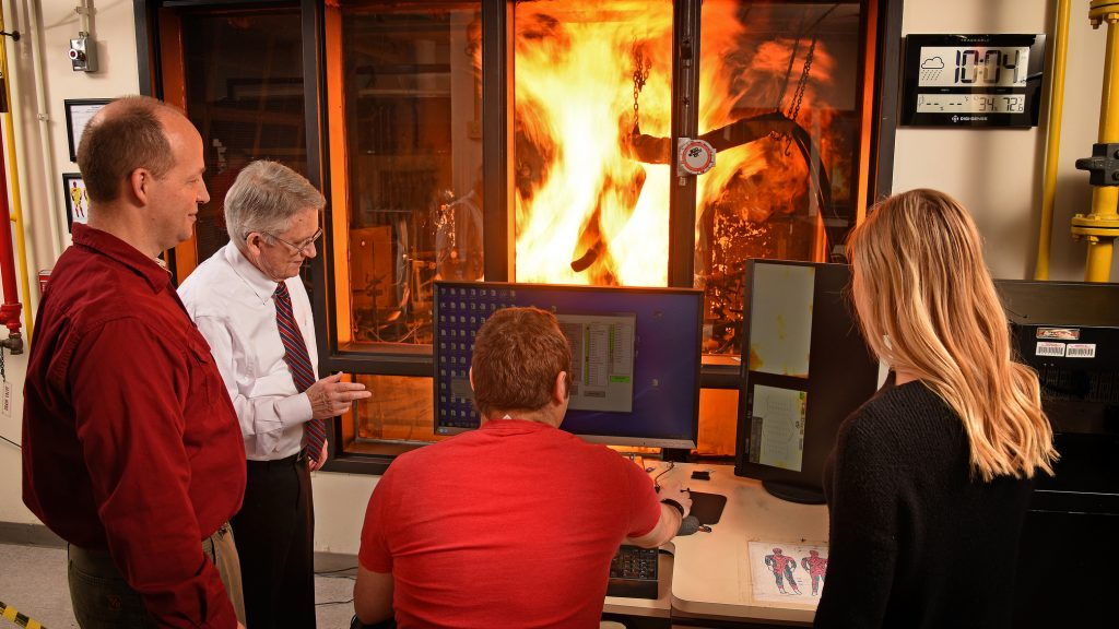Four people gathered around a computer watch a fire-resistant manikin that has been set aflame in a glass chamber