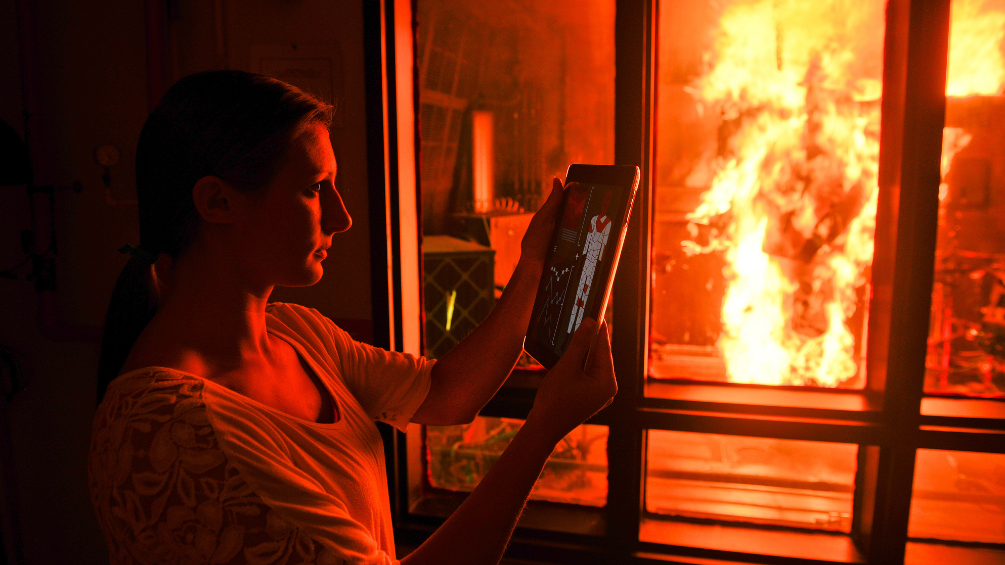A researcher looks at results on an iPad while the PyroMan manikin is aflame in a glass chamber