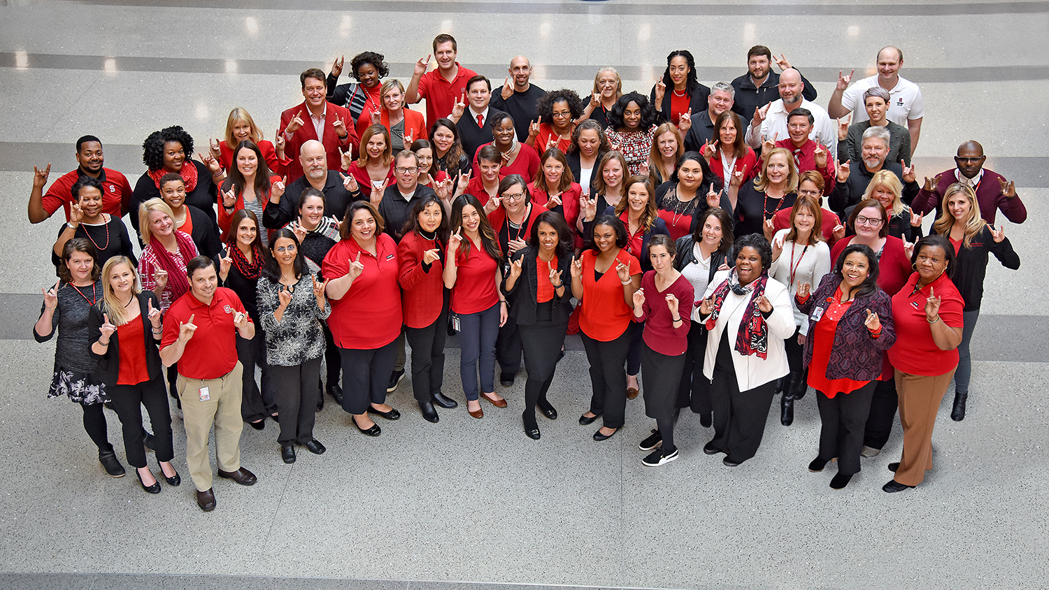 University Human Resources staff making the Wolfpack hand sign.