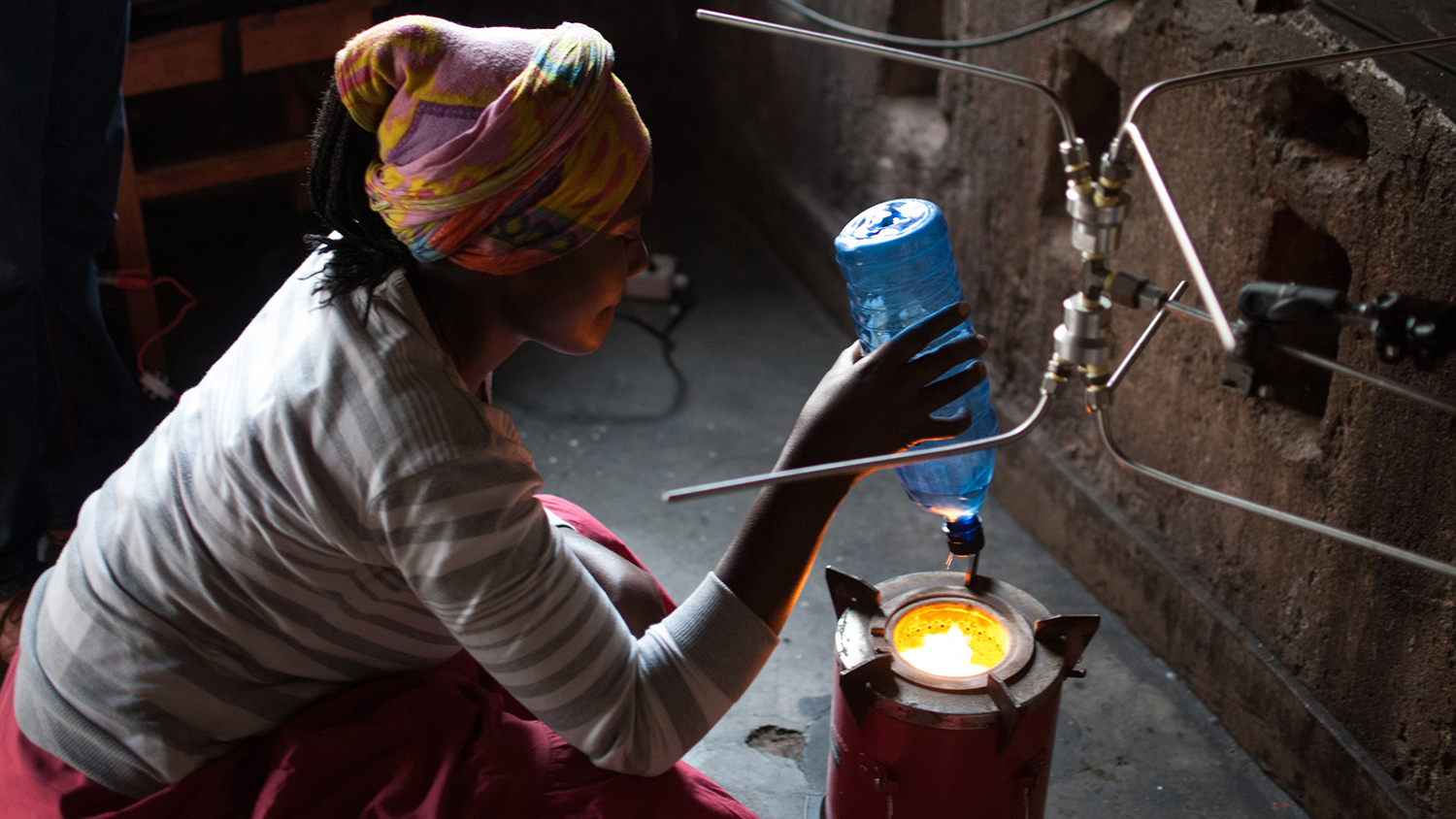 woman crouching by cookstove