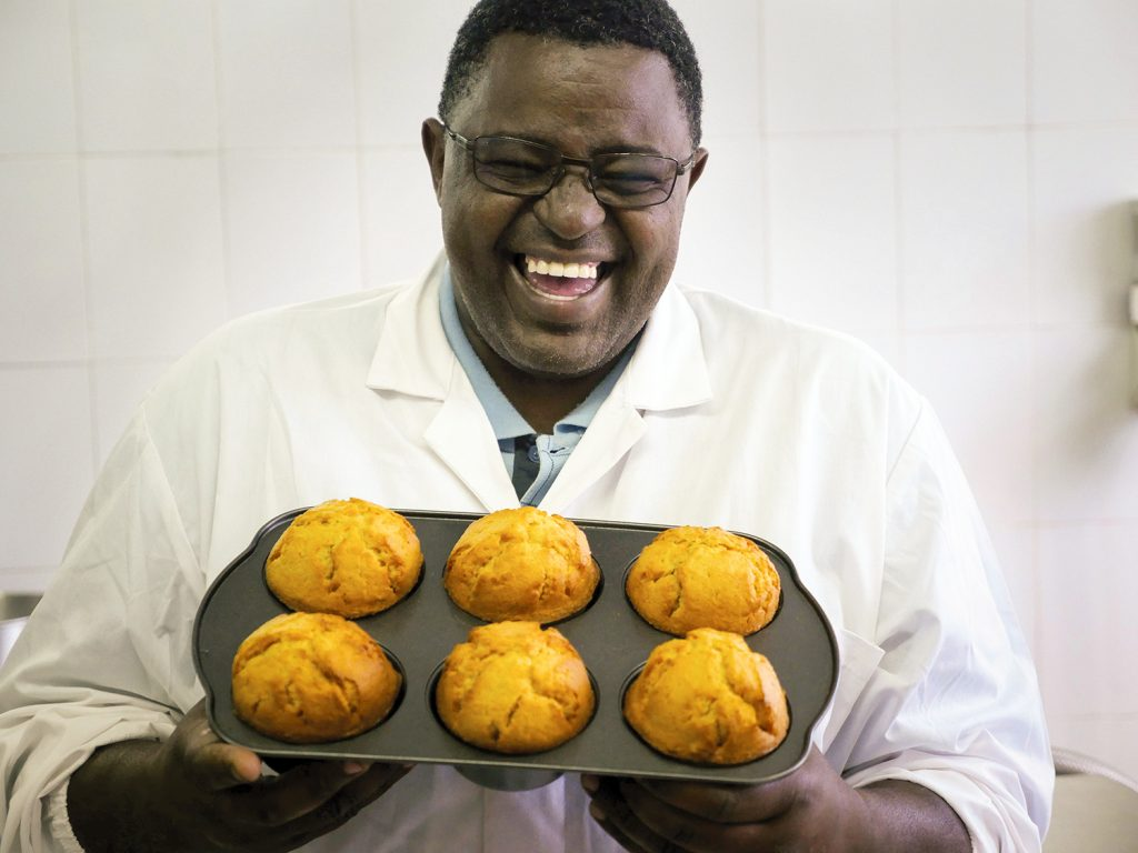 A man with a delighted smile holding a tray of sweet potato muffins.