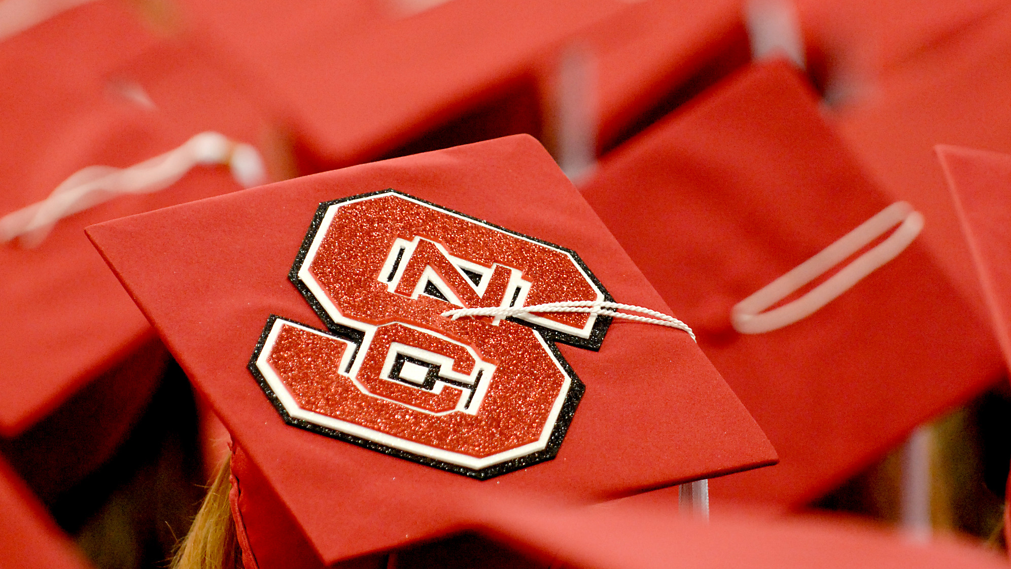 Shot of graduation caps, including one with NC State logo on the top