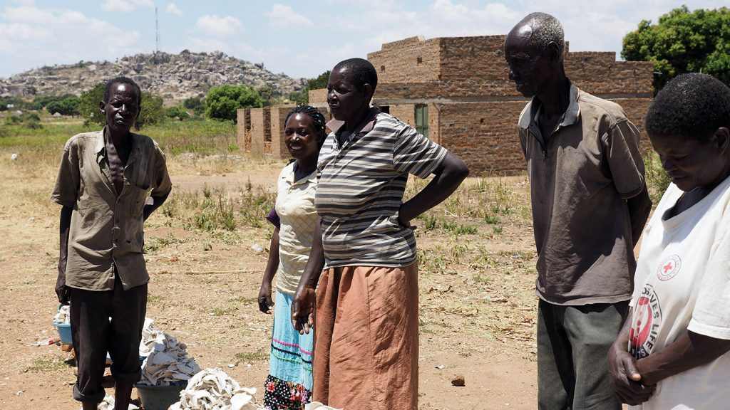 A group of roadside vendors selling dried sweet potatoes in Uganda.